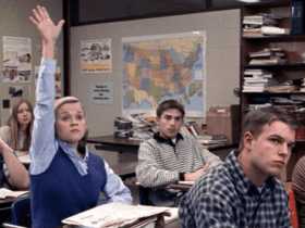 Young blonde raising her hand in a classroom