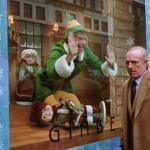 Man dressed as an elf in department store window. His dad is a holiday worker and can't see him
