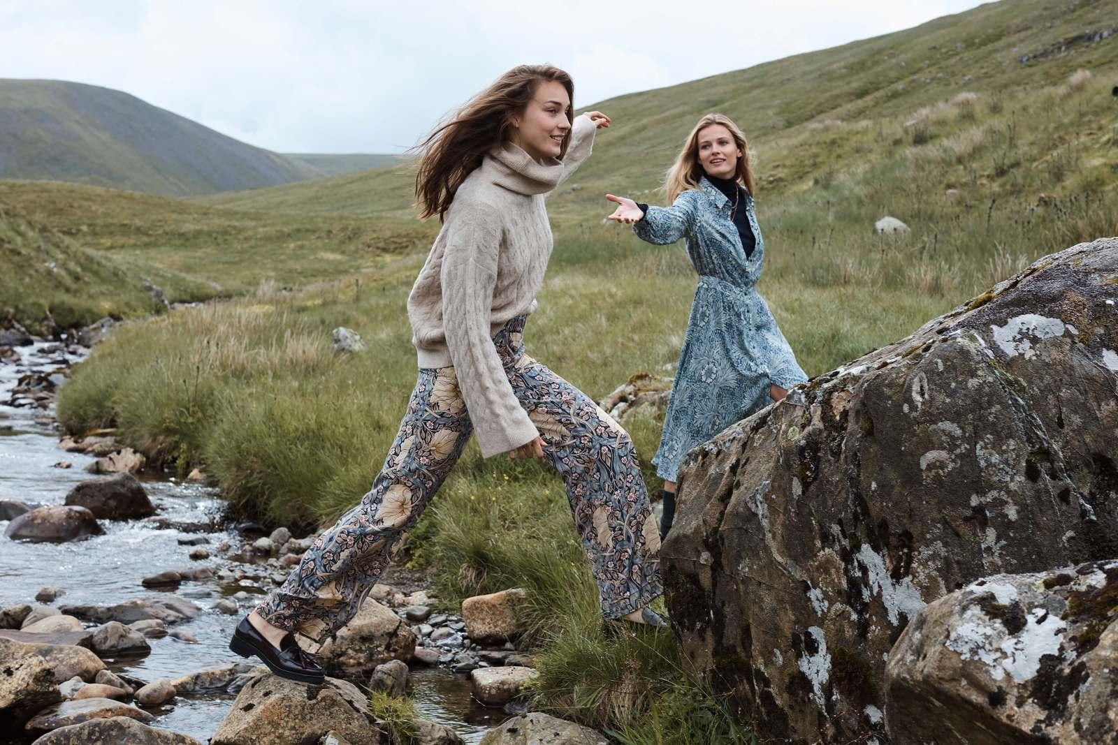 Two women in Morris prints walking by a stream