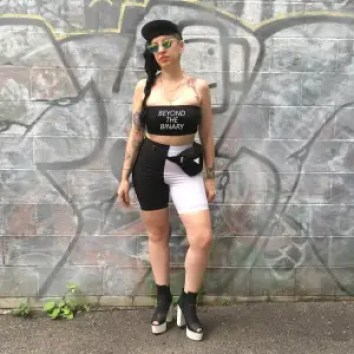 """Feminine presenting person in a black tube top that says """"beyond the binary"""""""