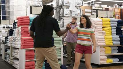 A white women and black man shake hands in bed bath and beyond