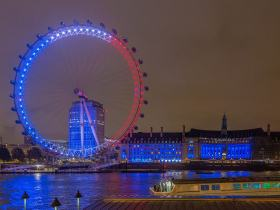 night view of the London Eye with French flag colored blue red and white lights