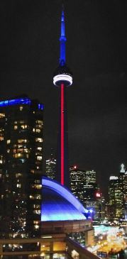 Tall tower at night lit like French flag