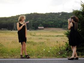 Young white woman in black dress pointing a camera at another young white woman in a black dress