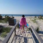 back of a white woman wearing a pink cover up, walking on a beach