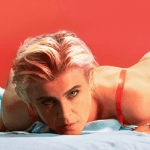 Album cover Robyn Honey Blonde woman lying on blue fabric with a red background