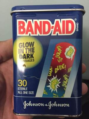 A box of glow in the dark bandaids work uniforms after party