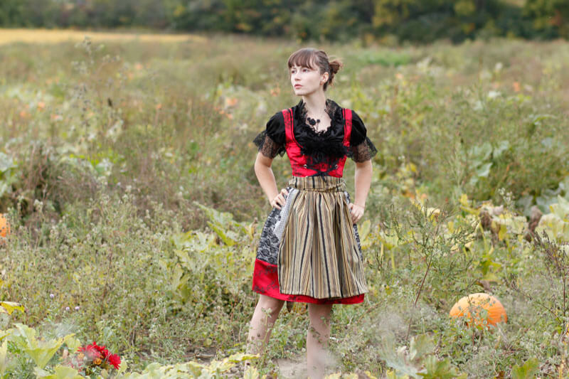 White women in red and black dirndl standing in a pumpkin field