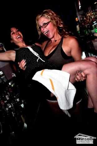 A women carrying another woman behind a bar. Work uniforms after party
