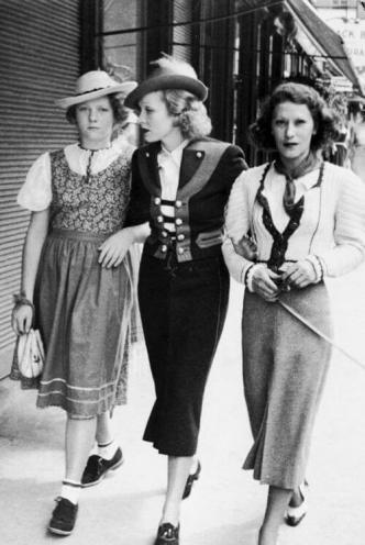 Black and white photo of Marlene Dietrich in Bavarian style costume and a girl in dirndl