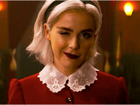 Close up of blonde woman wearing a red dress with Peter Pan collar