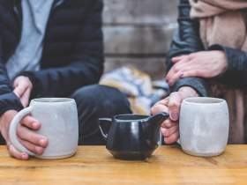 Two people in warm clothes holding tea cups Dry January