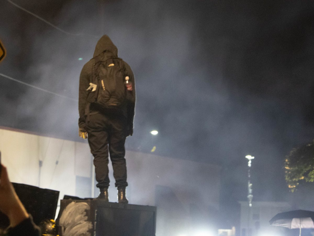 A black bloc protester stand with back to camera