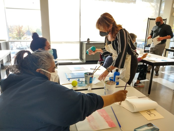 Students paint at their tables while the instructor prepares to pour teal paint out for one of the artists.