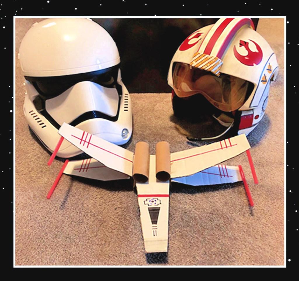 Una nave x-wing hecha de cartón junto a dos cascos de Star Wars