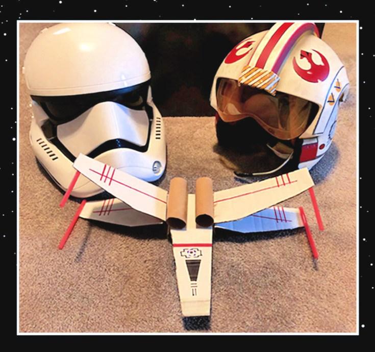 Nave x-wing hecha a mano junto a dos cascos de Star Wars