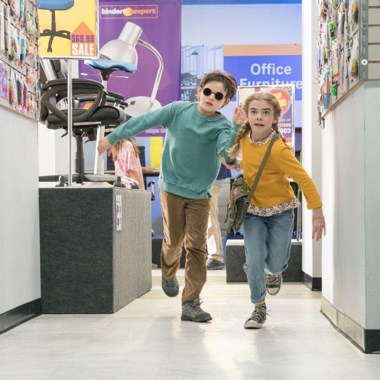 Dos niños corriendo en una tienda, el niño tiene lentes de sol y la niña una bolsa colgada de lado