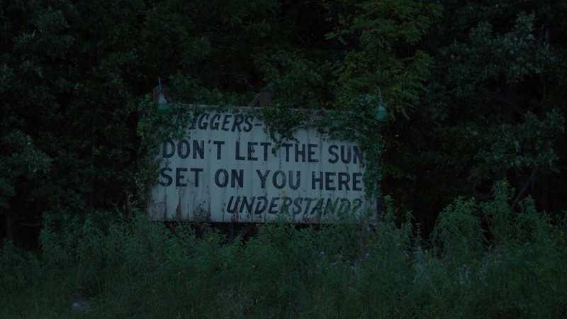 sign warning black people to go inside at sundown