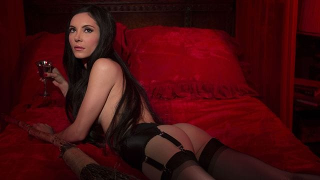 elaine lies on the bed in black lingerie
