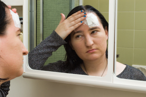 women looking in a mirror at a bandage on her forehead