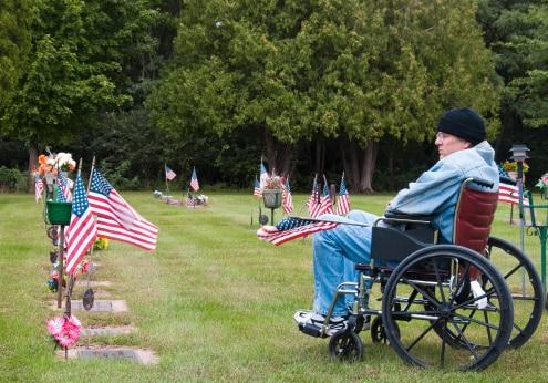 a handicapped veteran in a graveyard admiring fallin troops