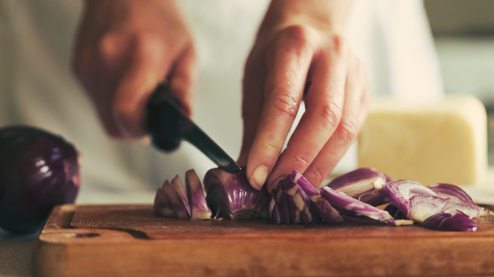 woman slicing red onion