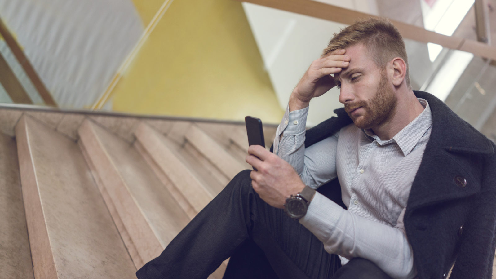 Businessman sitting on a staircase and using mobile phone while having a headache.