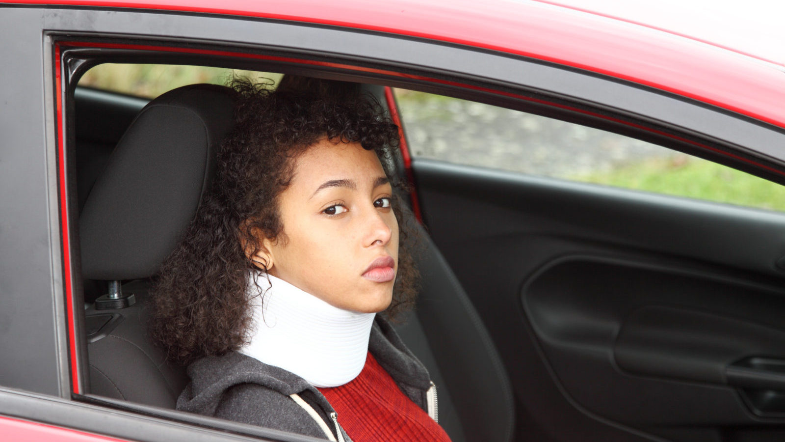 female wearing neck brace in car-whiplash insurance theme