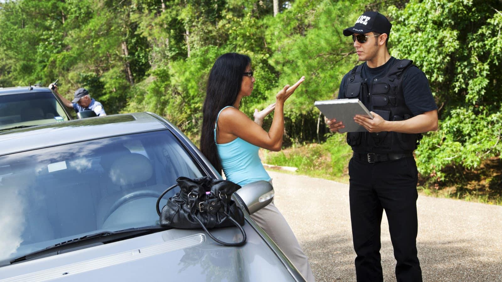 Policeman makes traffic stop. Woman explaining.
