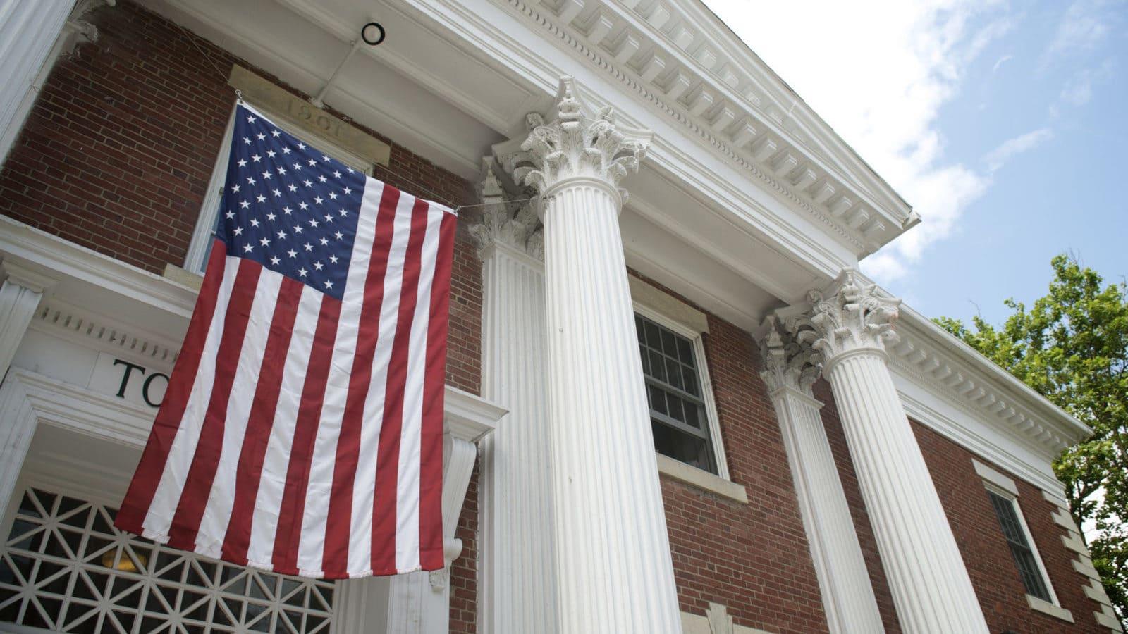American flag hangs between the white columns