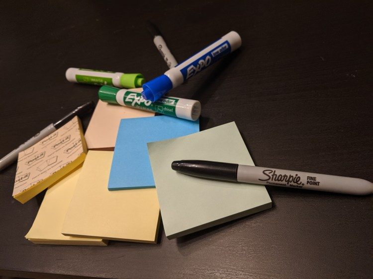 A small pile of colorful sticky notes with various colored dry erase markers and sharpies laying on a black table top