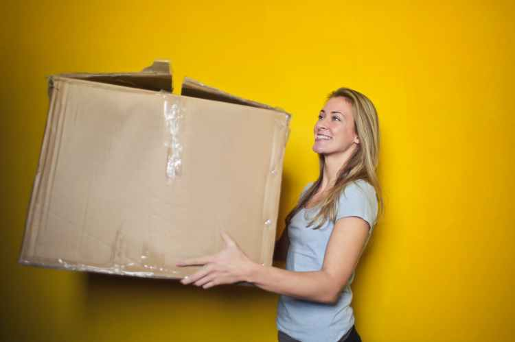 woman in a white shirt carrying a brown moving box in front of a yellow wall
