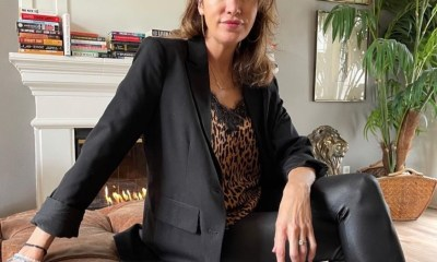 Natalie Plain sits on a couch wearing leather pants, leopard top and a blazer.