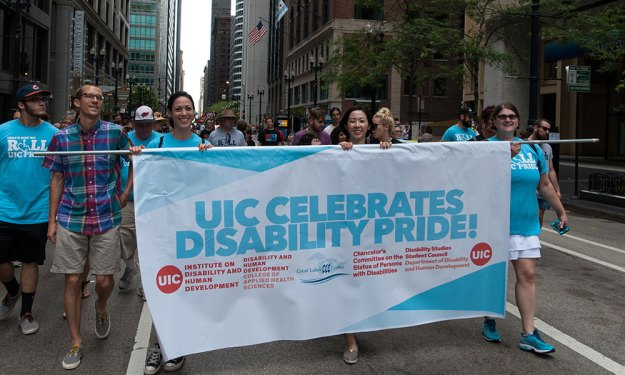 UIC DHD students, faculty and staff holding a banner in a parade that says UIC celebrates disability pride! Listed under these words: Institute on Disability and Human Development; Disability and Human Development College of Applied Health Sciences; Great Lakes ADA Center; Chancellor's Committee on the Status of Persons with Disabilities; Disability Studies Student Council, Department of Disability and Human Development. On each side of the banner is a circle with UIC in the middle.