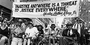 "Black and white photo of a 1993 disability rights march in New York City. At front are Paul Miller, Judy Heumann, Justin Dart, and others, with large crowd behind. Marchers holding a sign that says: ""Injustice anywhere is a threat to justice everywhere."" Photo credit: Tom Olin."