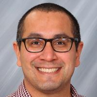 Image of David Hernandez Saca - Headshot of an individual with short cut and wearing black frame glasses. The individual is smiling at the camera