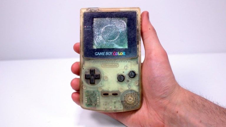 Someone holding a dirty game boy color