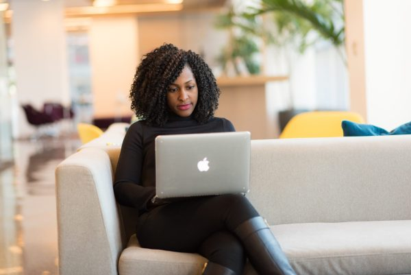 woman sitting on couch working with her laptop