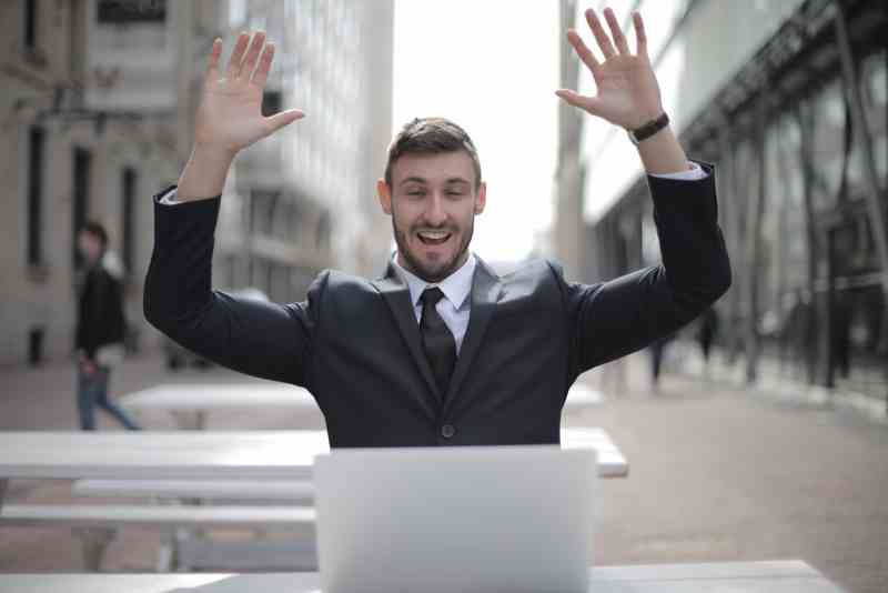 Man with suit celebrating while working on his laptop.