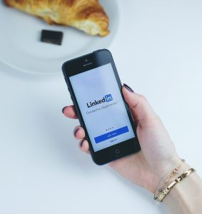 Woman holding her phone while selecting LinkedIns app
