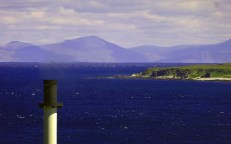Mull from Caol ila with the distillery chimney freshly painted in the foreground