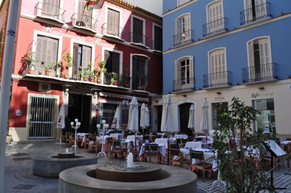Cellar Worthy Wine An outdoor seating area on the square in Ronda Spain, White tabel cloths and umbrellas against buildings of red and blue.