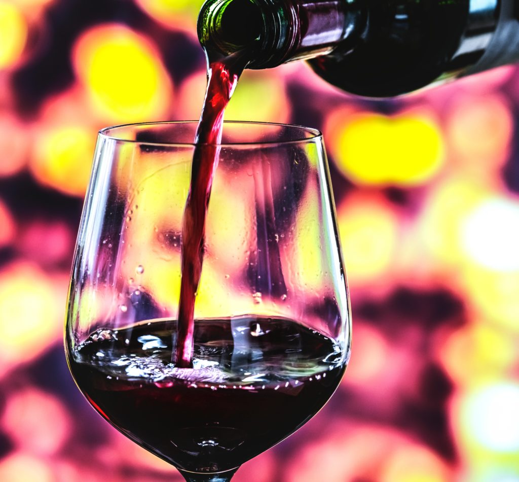 Cellar Worthy Wine A wine glass being filled with a deep red wine against an unfocused background of deep reds and yellows enhancing the first pour of extraordinary wine