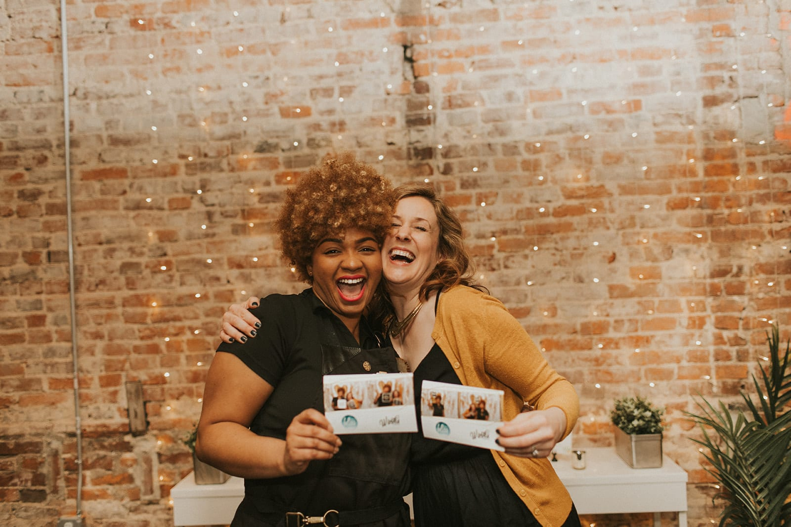 Shelly Pate Photography captured this candid photograph of Sara, owner of District Bliss, and Chrissy, owner of Charismatic Creations, holding their Winks Photo Booth pictures and laughing at The Gallery at Elevate in DC