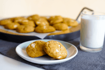 Two chewy pumpkin brown butter white chocolate chunk cookies on a dessert plate next to a glass of milk and tray of fresh cookies.