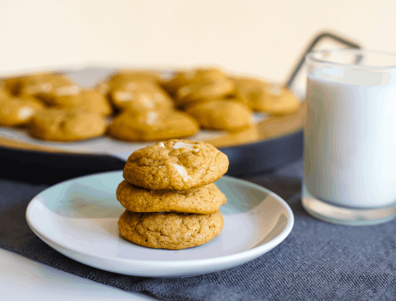 Three chewy pumpkin brown butter white chocolate chunk cookies stacked on top of each other next to a glass of milk and tray of more cookies..