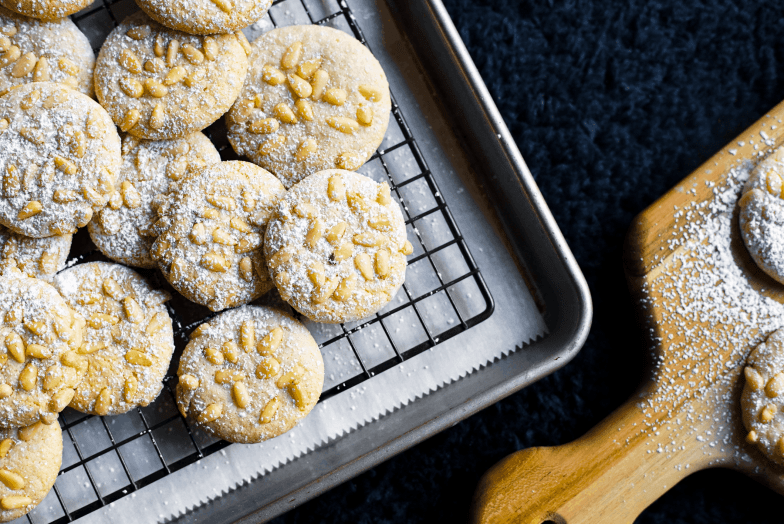 Batch of freshly baked Italian pignoli cookies dusted with powdered sugar.