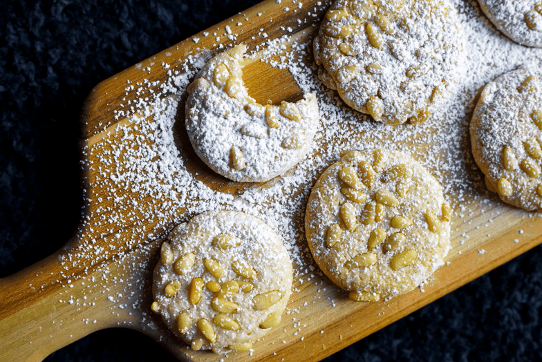 Rustic wood platter of Italian pignoli cookies—one with a bite missing—dusted with powdered sugar.