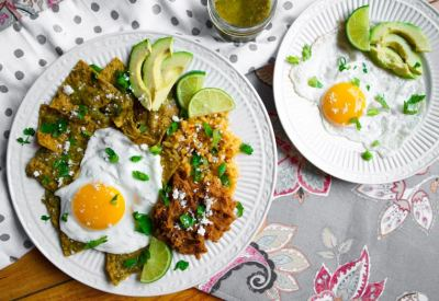 Plate of air fryer chilaquiles verdes with a sunny side up egg next to a jar of salsa and extra plate of eggs.