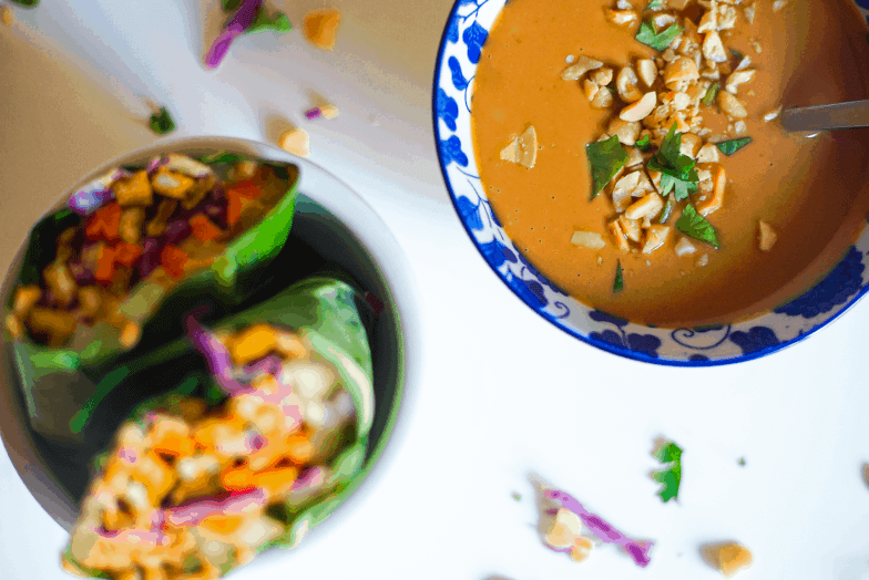 A bowl of peanut sauce garnished with cilantro and chopped peanuts next to a colorful vegetarian rainbow wrap made from collard green leaves.